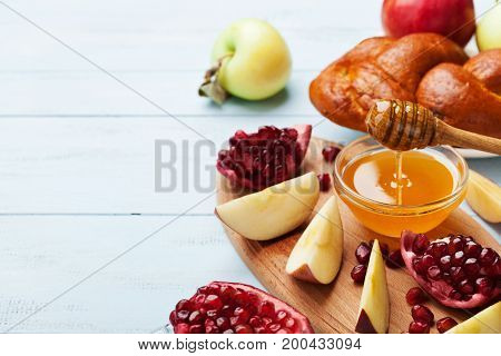 Honey apple slices pomegranate and hala serve on wooden kitchen board. Table set with traditional food for Jewish New Year Holiday Rosh Hashana. Copy space for text.