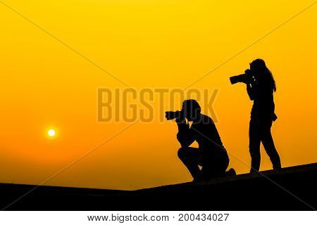 Silhouette of a girl and a man photographer with DSLR camera and tele lens at sunset on rooftop. Photographer life concept.