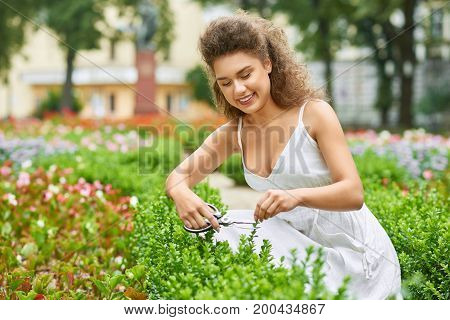 Beautiful young woman smiling happily gardening outdoors copyspace nature lifestyle positivity hobby garden concept.