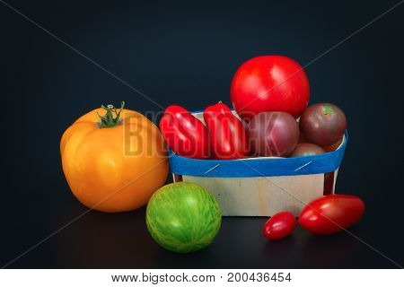 Assortment organic vegetable colorful tomatoes on black background