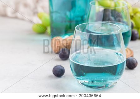 Trendy blue moscato wine in glass green and red grape on background horizontal copy space
