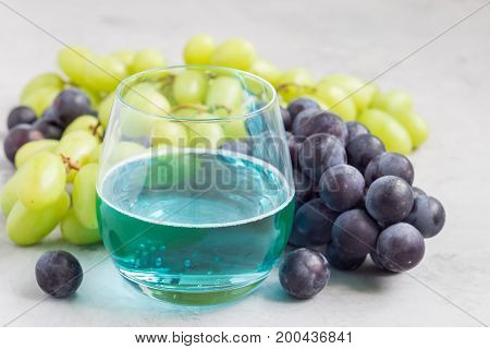 Trendy blue moscato wine in glass green and red grape on background horizontal