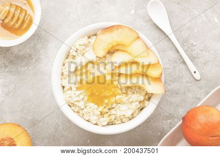 Oatmeal With Nectarine And Honey On A Gray Background. Top View. Food Background
