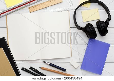 Stationery supplies in modern office workspace. Top view on open blank notebook, pen, pencil, rulers, small notepads and memo pads, headphones on white wooden desktop, flat lay, copy space, mockup