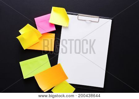 School stationery. Top view on colorful sticky blank notes and empty note paper on black background. Mockup for check-list with copy space