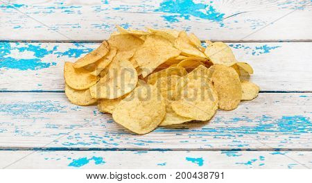 Heap of potato chips on the wooden background.
