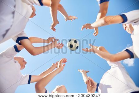 Low angle portrait of junior football team standing in circle with ball flying against blue sky