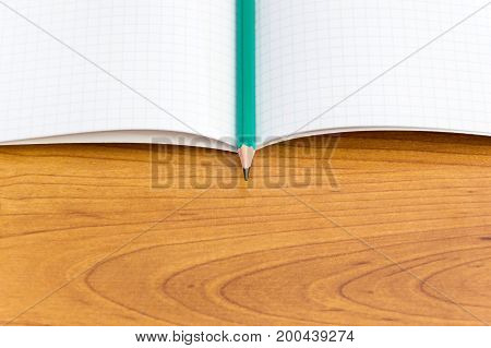 Pencil with copybook on the wooden table.