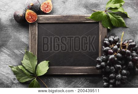 Black Slate Board And Autumn Harvest - Dark Grapes And Fig On A Dark Background. Top View, Copy Spac