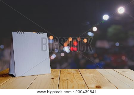 White calendar on wood table on dark light bokeh background and copy space mock up.
