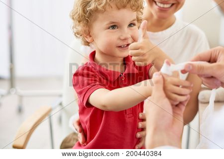 Portrait of adorable curly child showing thumbs up at doctors office during visit with mom