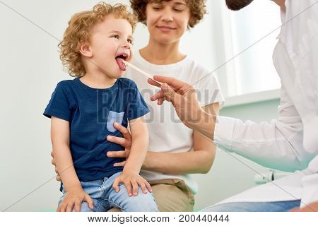 Portrait of cheerful little boy opening mouth for checkup at doctors office, sitting in mothers lap