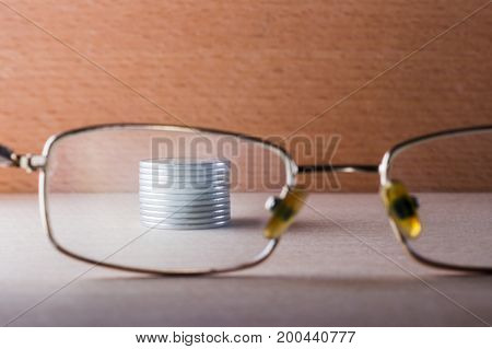 Shiny silver coins through a transparent glass of eye glasses on a wooden background