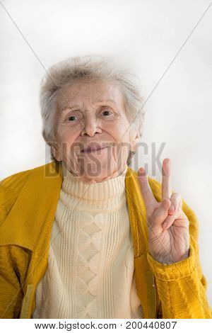 Portrait of a smiling elderly woman with a beautiful smile, hand shows peace