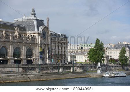 ParisFrance- April 30 2017: View of the Orsay Museum from the Royal Bridge. On the waterfront people walk