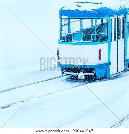 back of the tram car in winter on rails almost covered with snow