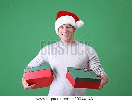 Handsome man in Christmas hat holding gift boxes on color background