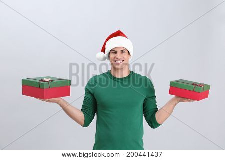 Handsome man in Christmas hat holding gift boxes on light background