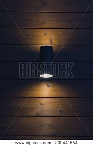 Wall lamp on a wooden wall in the evening light. Interior
