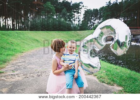 young mother tickling her laughing son in the park