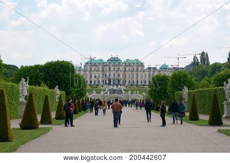 VIENNA, AUSTRIA - APR 30th, 2017: Beautiful building of upper Belvedere Palace on a sunny day with blue sky and clouds in summer and tourists walking.