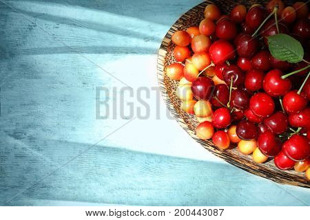 Plate with fresh ripe cherries on wooden background