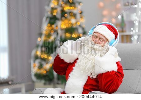 Santa Claus listening to music in living room