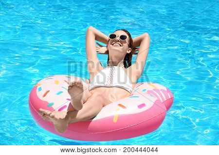Beautiful young woman relaxing on inflatable donut in blue swimming pool