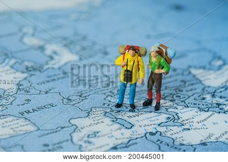 miniature figures with backpack walking on map as Travel concept.