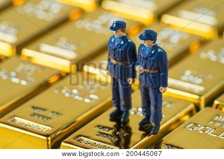 selective focus on miniature security guard standing on shiny gold bullion as security or wealth concept.
