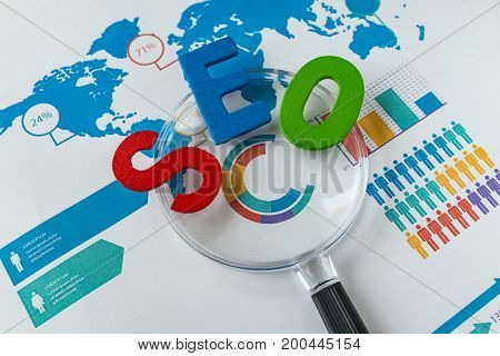 Search engine optimization concept as colorful alphabet abbreviation SEO on magnification glass on printed analysis chart and graph.