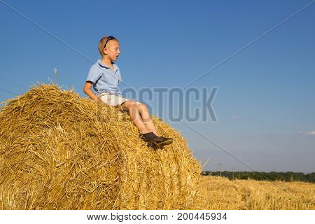 The boy sat with his eyes closed on a bale of hay