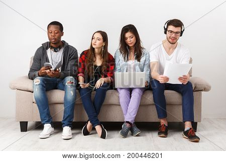 Friendship and education. Young diverse people listen to music with gadgets, sitting together on couch indoors