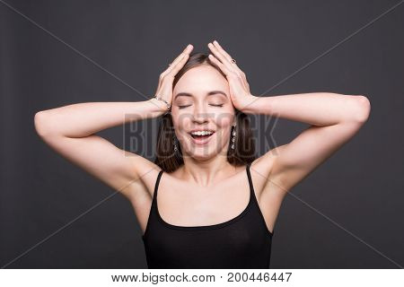 Portrait of excited laughing attractive woman holding her head. Beautiful girl having fun, dark background