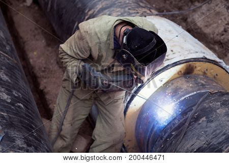 Repair of heating duct. The workers welders made by electric welding and gas welding on large iron pipes at a depth of excavated trench.