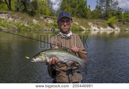 Fisherman with asp fish trophy on river background