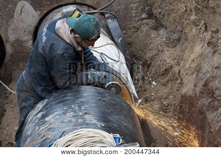 Odessa, Ukraine - October 11, 2016: Sparks From Cutting Metal. Repair Of Heating Duct. The Workers,