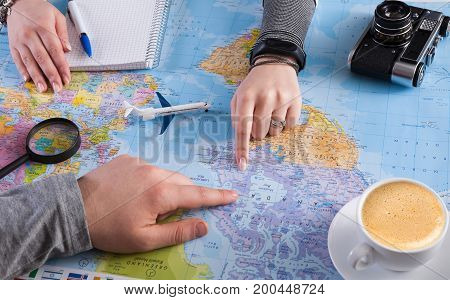 Couple planning airplane trip to Canada, point on map, taking notes in blank notebook, copy space