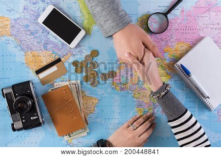 Agreement in choosing travel, top view. Man and woman handshake above world map with tourist stuff