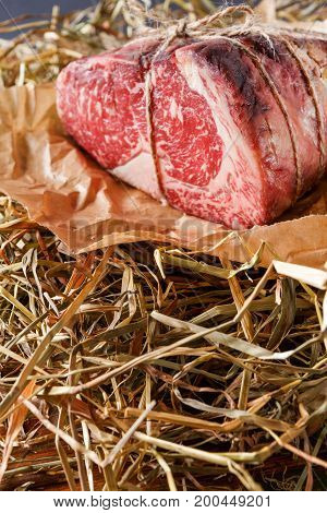 Raw black angus beef bound with rope in craft paper on straw. Aged prime marble meat closeup, vertical
