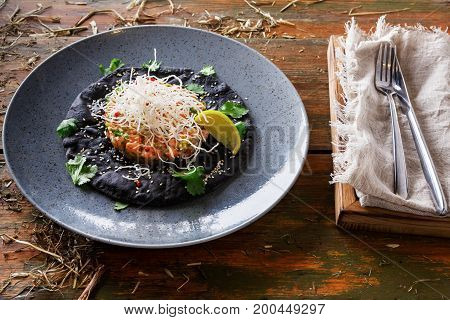 Exclusive restaurant food. Traditional hawaiian appetizer - poke with fresh salmon on black sesame flat cake on gray plate and cutlery aside, served in rural style. Organic meals on wooden background
