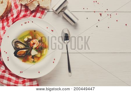 French cuisine restaurant. Seafood soup with white fish, shrimps and mussels in plate sprinkled with spices. Fresh exclusive meals on white wood with checkered cloth and cutlery, top view, copy space