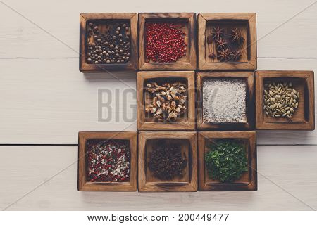 Spices assortment on white rustic background. Wooden boxes with flavorings making frame. Salt, peppers, coriander seeds, cloves, walnuts and green parsley, copy space