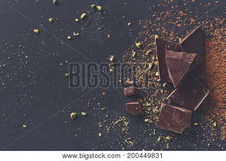 Sweet background. Broken pieces of dark bitter chocolate, cocoa powder and pistachio crumble on black stone surface, top view, copy space