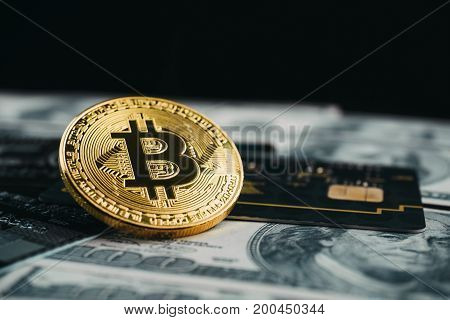 Golden bitcoin with credit card on top of dollar banknote background new currency accepting bitcoin for payment finance concept