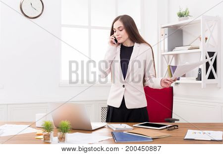 Young businesswoman talking by phone with papers, standing at modern office workplace. Business consulting.