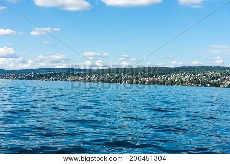 Lake Water View With Urban City Area And Mountain And Blue Sky