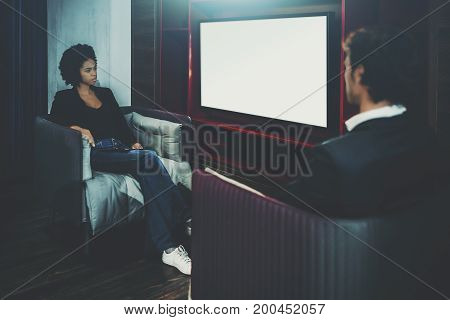 Young cute black woman with curly afro hair is sitting in modern armchair opposite caucasian man and looking on mock-up of modern TV with blank white screen for your advertising or message