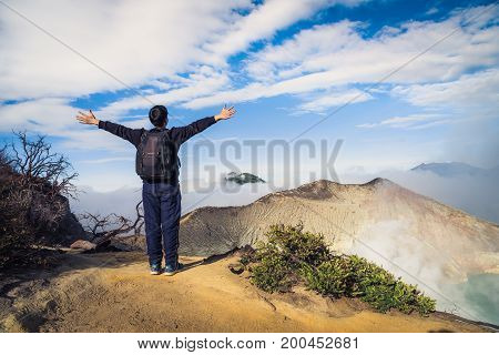 Hiker or Traveler with backpack standing on top of a mountain with raised hands and enjoying sunrise Landscape view of Kawah Ijen at Sunrise. The most famous tourist attraction in Indonesia.