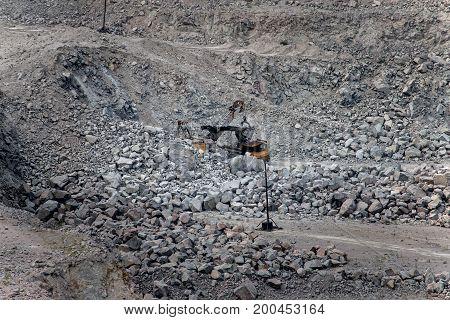 Excavator loading granite or ore into dump truck at opencast Ukraine Zaporozhye.